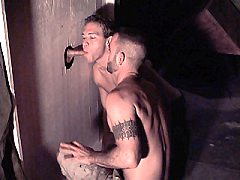 Tattoed sexy gay sucking a huge hard cock dipping in a glory hole orgy