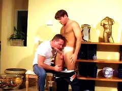 Homosexual musclemen couple manifesting a lust-filled act in the living